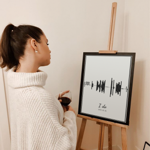 A woman holding wine glass and looking at the poster